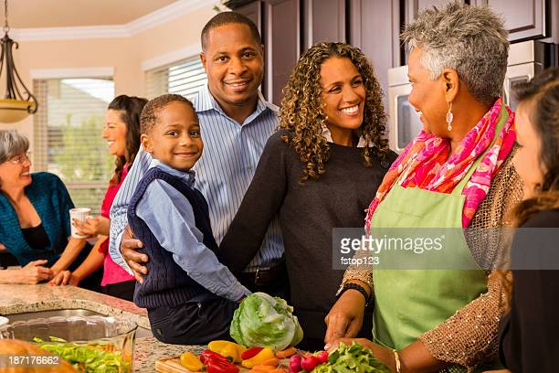 Relationships: Multi-generation family prepares dinner in kitchen.