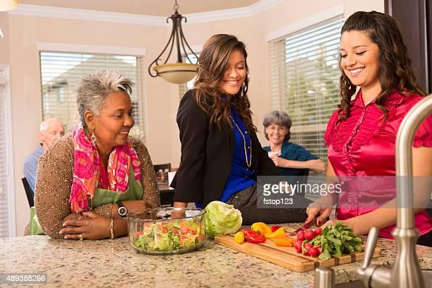 Las relaciones entre: Mujer mayor, la familia y los amigos que cocinan en casa cocina.