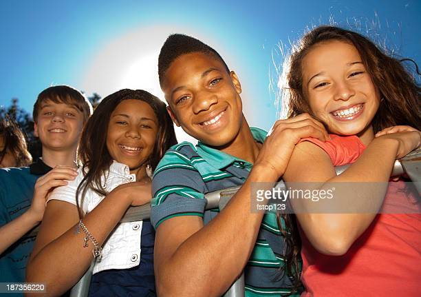 Relationships: Teenagers smiling in a row against clear blue sky