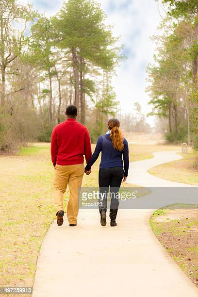 Relationships: Young African descent couple hold hands, walk outside park.