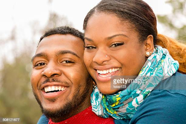 Relationships: Young African descent couple playful outside. Happy, laughing.