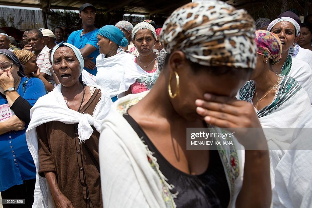 Relative and friends grieve on July 22 2014 during the funeral of 39yearold Israeli army tracker soldier Bansayan Kesahun in the southern town of...