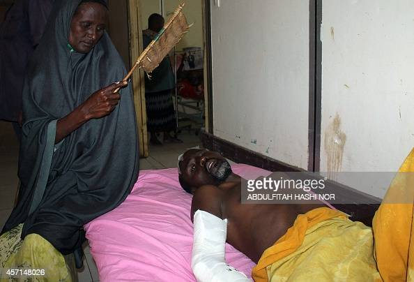 A relative comforts a victim admitted at Madina hospital in Mogadishu on October 13 2014 where hospital officials confirmed that one of the 32...