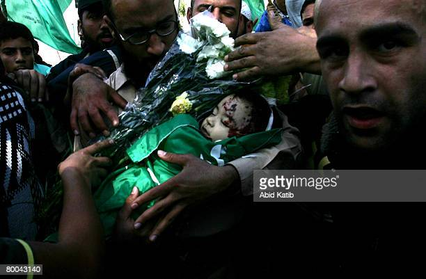 A relative hands out flowers as the body of fivemonth old Mohammad Naser AlBuri is carried by his father during his funeral February 28 2008 in Gaza...