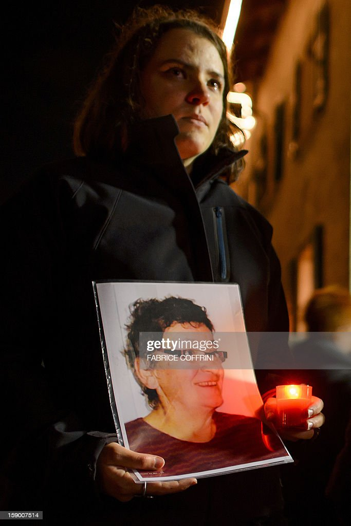 A relative holds a picture of one of the woman killed during a march on January 5, 2013 in memory of the victims of a shooting in the village of Daillon. A gunman with psychiatric and drug problems killed three women and wounded two men on January 3, 2013 in a shooting spree in the tiny village where he lived in the mountains of southern Switzerland. Police shot and wounded the suspect after he threatened them with a gun following the attack in Daillon that raised fresh questions about the country's liberal gun ownership laws.