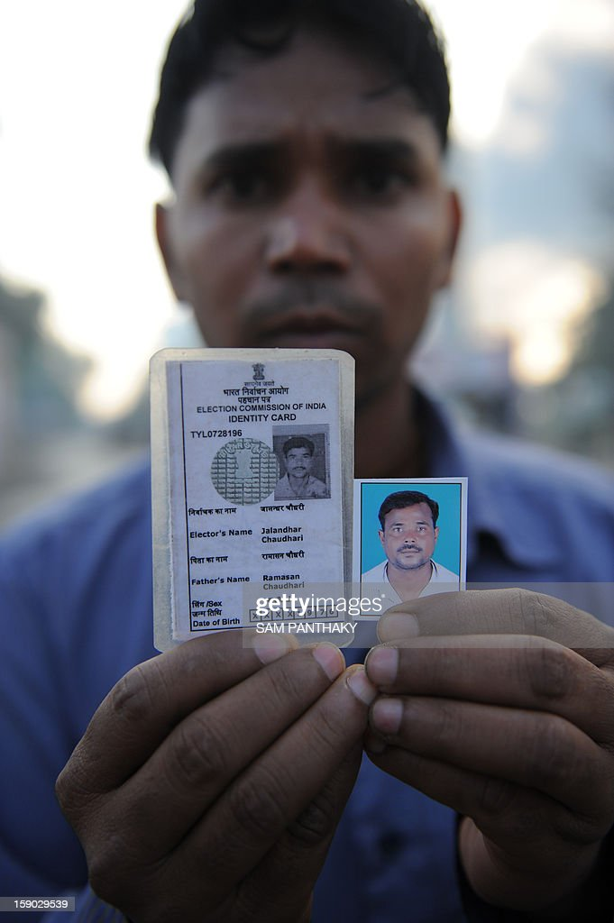 A relative holds up a photograph of missing worker Jalandhar Chaudhari during a fire at the Indian Oil Corporation (IOC) plant at Hajira near Surat, some 275 kms from Ahmedabad on January 6, 2013. Three persons were killed in a major fire in a storage tank of IOC terminal, which was contained after a 21-hour operation by fire brigade team, officials said according to the Press Trust of India (PTI). AFP PHOTO / Sam PANTHAKY