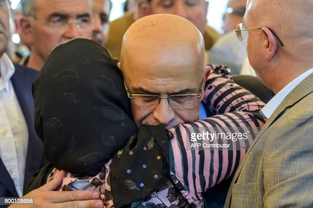 A relative hughs former journalist turned CHP lawmaker Enis Berberoglu during his stepfather's funeral ceremony on June 23 2017 in Istanbul Turkey's...