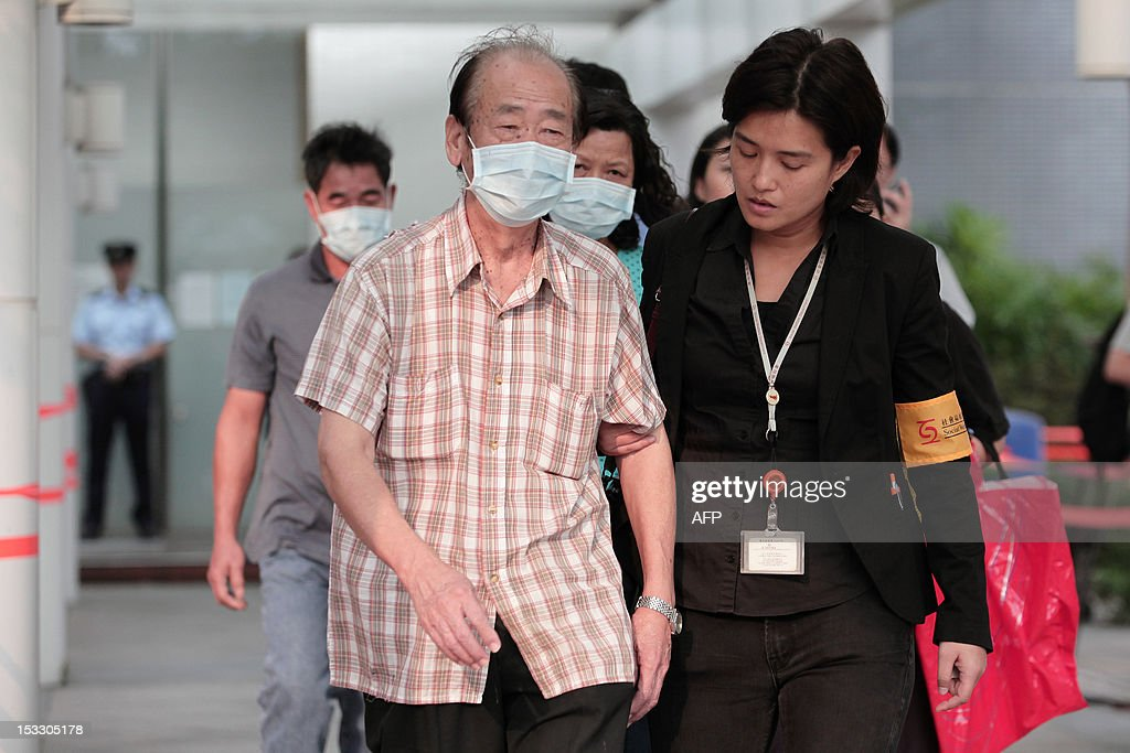 A relative (front L) is helped by a social worker (front R) as he leaves the Kwai Chung public mortuary after identifying a victim of a boat collision in Hong Kong on October 3, 2012, two days after a ferry collided with a pleasure boat killing at least 38 people a short distance from Lamma island. More than 120 passengers and crew were on the Hong Kong Electric company's Lamma IV to watch a huge National Day fireworks display in Victoria Harbour when the accident occurred just off Lamma, an island to the southwest of Hong Kong.