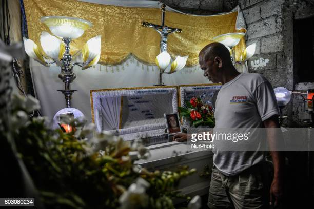 A relative looks at the coffin of Marvin Ocampo who relatives say was a drug user during his funeral wake in Navotas north of Manila Philippines June...