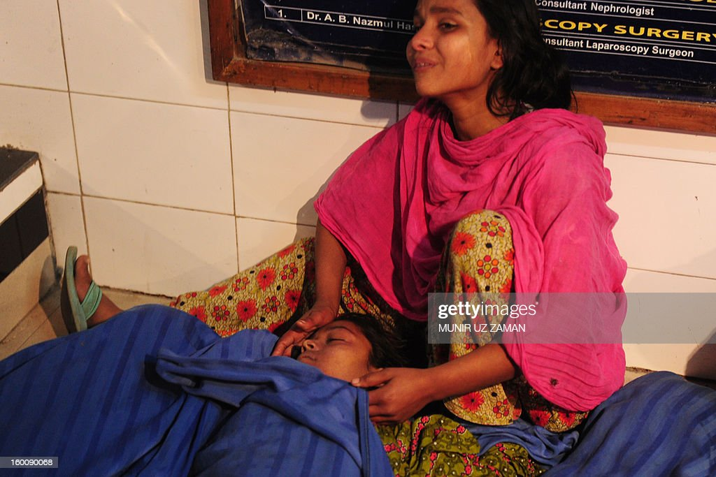 A relative mourns over her sister's body at a hospital following a blaze at a garment factory in Dhaka on January 26, 2013. At least six workers at a garment factory in the Bangladeshi capital were killed in a stampede as a fire broke out. AFP PHOTO/Munir uz ZAMAN