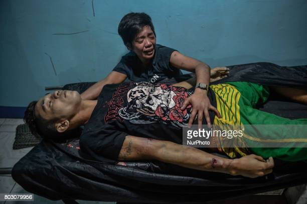 A relative mourns over the body of Julius Soriano who was shot dead by police following a police operation against illegal drugs inside a morgue in...