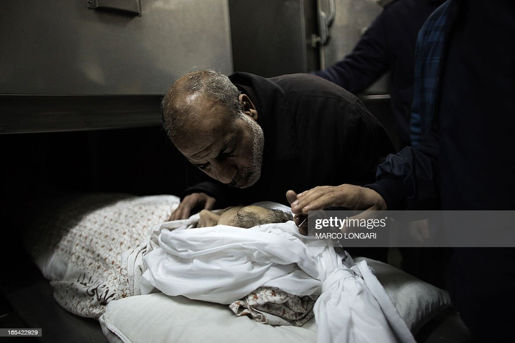 A relative mourns over the body of Maisara Abu Hamdiyeh, a Palestinian prisoner who died of cancer while in Israeli detention, at Al-Ahli hospital in the West Bank city of Hebron ahead of his funeral on April 4, 2013. The Palestinian leadership has accused Israel of medical negligence, despite moves by the prison service to secure his early release on compassionate grounds, with news of his death sparking angry clashes with the army, notably in Hebron.