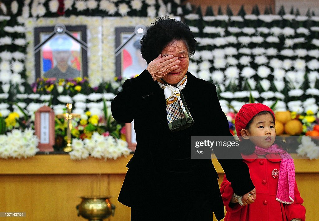 A relative of a marine who was killed in a North Korean artillery barrage on the South Korean border island of Yeonpyeong weeps during a memorial...