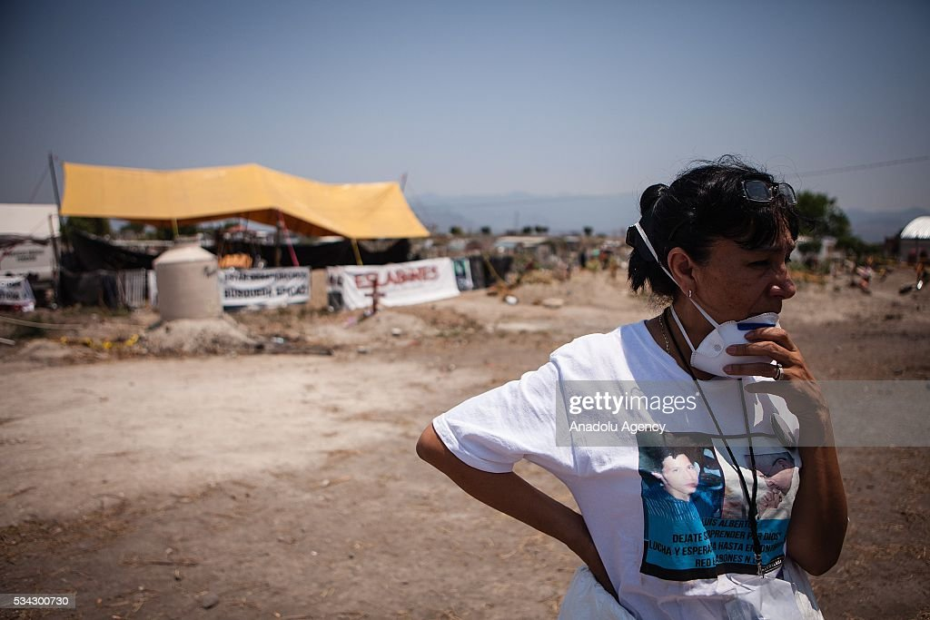 A relative of a missing persons is seen in the graves where 116 bodies were found buried in Tetelcingo, Mexico on May 25, 2016.