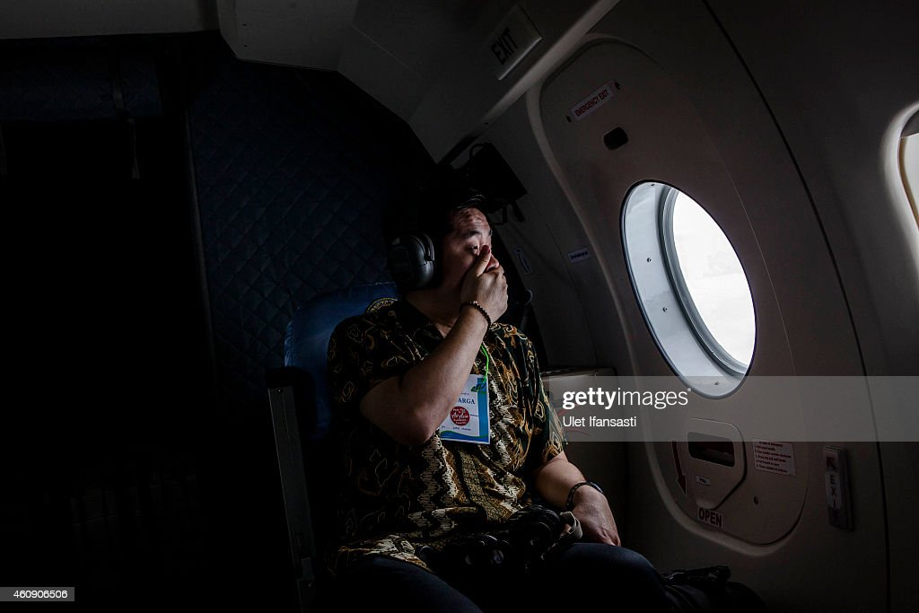 A relative of a passenger looks out over the waters of the Java Sea near Pangkalan Bun Kalimantan on December 30 2014 in Surabaya Indonesia Debris...