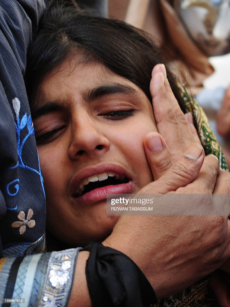 A relative of a slain policeman mourns during the funeral of lawmaker Manzar Imam and his guards in Karachi on January 18, 2013. Shops, businesses and schools shut Friday across Pakistan's financial capital Karachi, braced for further unrest after the killing of a politician and a night of sporadic shootings. AFP PHOTO/Rizwan TABASSUM