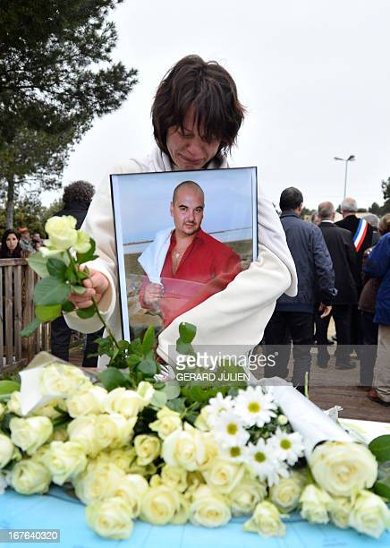 A relative of a victim holding his portrait cries as she lays a rose at the end of a march in homage to the three men killed by an apparently...