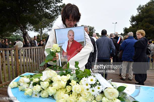 A relative of a victim holding his portrait lays a rose at the end of a march in homage to the three men killed by an apparently deranged teenager on...