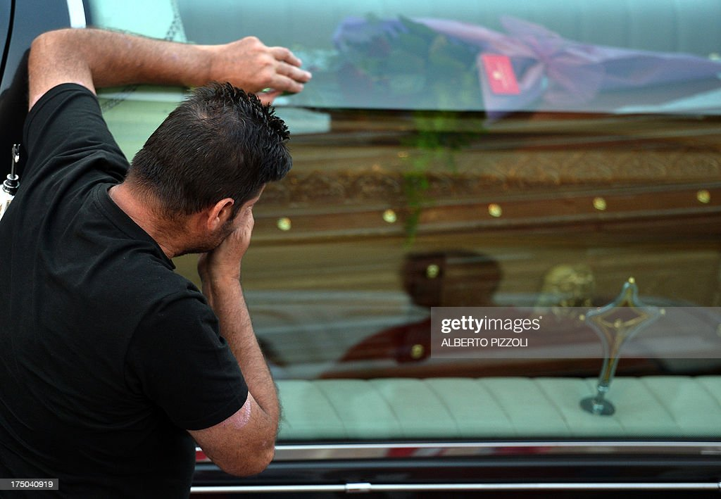 A relative of a victim of a bus crash on the road between Monteforte Irpino and Baiano mourns over a coffin on July 29, 2013, near the morgue in Monteforte Irpino, southern Italy. A coach carrying pilgrims plunged off a motorway flyover near Naples in southern Italy, killing at least 39 people in one of the worst such accidents in Europe in recent years.