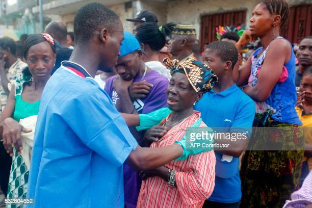 A relative of a victim of the mudslide is comforted at the Freetown Morgue Sierra Leone on August 16 2017 Sierra Leone began a weeklong period of...
