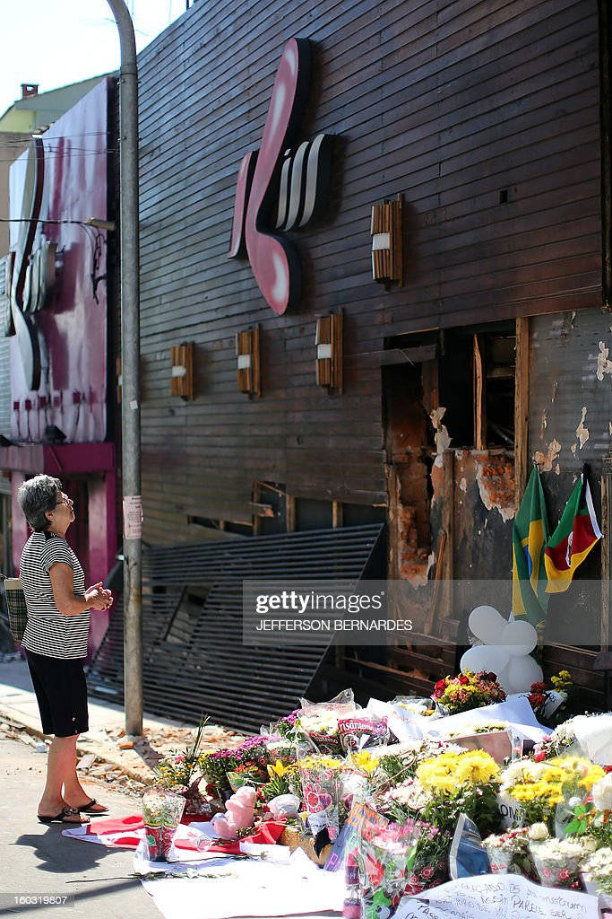 A relative of a victim stands by flowers put in front of the Kiss nightclub in Santa Maria, southern Brazil on January 29, 2013 where a blaze Sunday early morning left a death toll of over 230. Police in Brazil arrested four suspects Monday after a nightclub fire killed 231, left dozens more clinging to life, and forced officials to defend readiness for the Olympics and World Cup.
