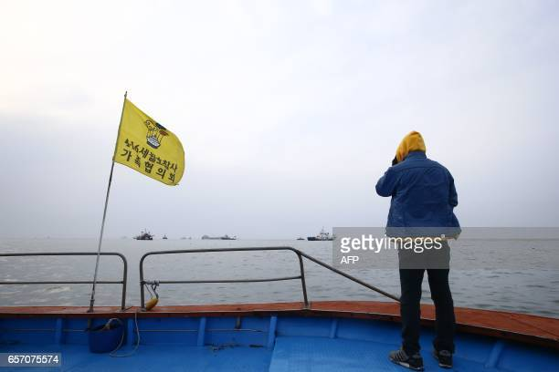 TOPSHOT A relative of a victim watches the ongoing salvage operation of the Sewol ferry off the coast of South Korea's southern island of Jindo on...