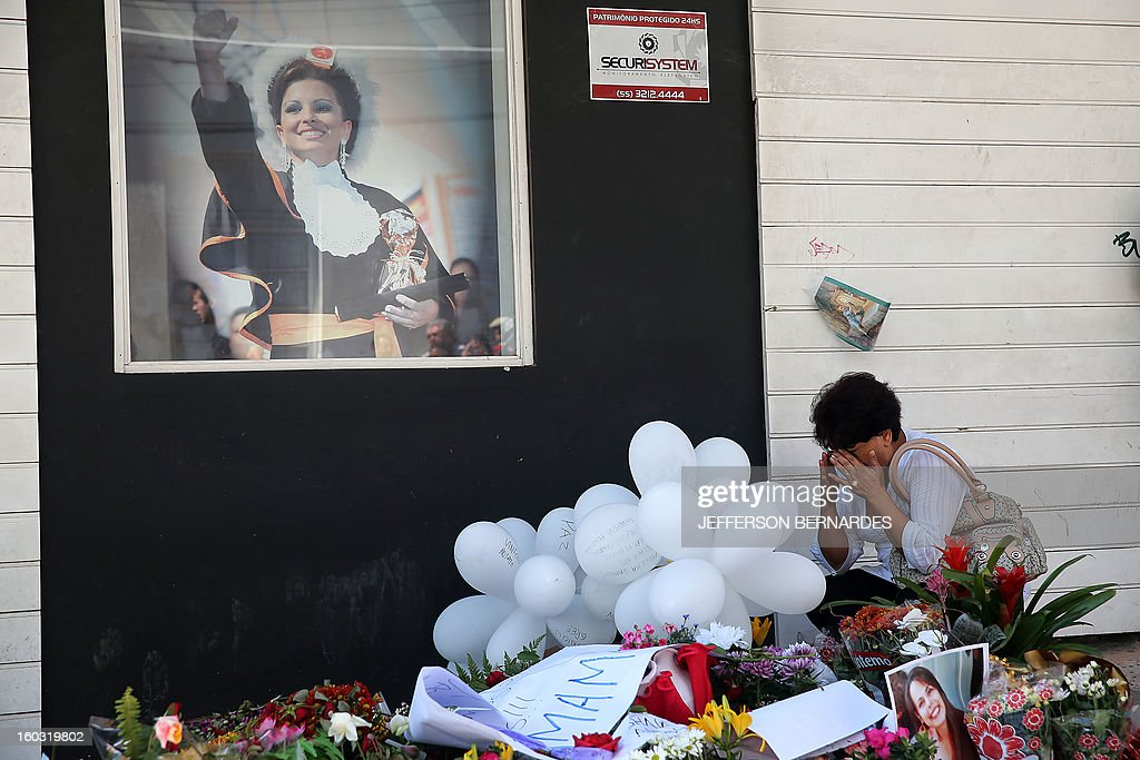 A relative of a victim weeps by flowers put in front of the Kiss nightclub in Santa Maria, southern Brazil on January 29, 2013 where a blaze Sunday early morning left a death toll of over 230. Police in Brazil arrested four suspects Monday after a nightclub fire killed 231, left dozens more clinging to life, and forced officials to defend readiness for the Olympics and World Cup.AFP PHOTO / JEFFERSON BERNARDES