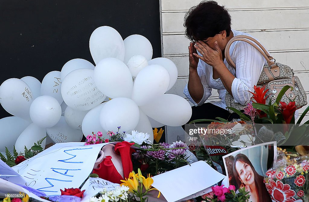 A relative of a victim weeps by flowers put in front of the Kiss nightclub in Santa Maria, southern Brazil on January 29, 2013 where a blaze Sunday early morning left a death toll of over 230. Police in Brazil arrested four suspects Monday after a nightclub fire killed 231, left dozens more clinging to life, and forced officials to defend readiness for the Olympics and World Cup. AFP PHOTO / JEFFERSON BERNARDES