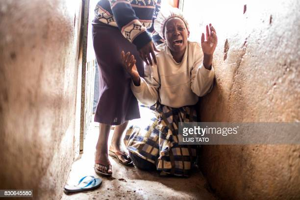 TOPSHOT A relative of a young girl allegedly killed by gunshot injury in the balcony of his house reacts at Mathare slums in Nairobi on August 12...