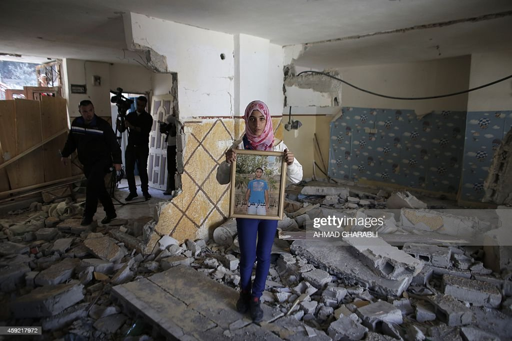 A relative of Abdelrahman Shaludi a Palestinian who killed two Israelis with his car last month displays his portrait inside his family home after it...
