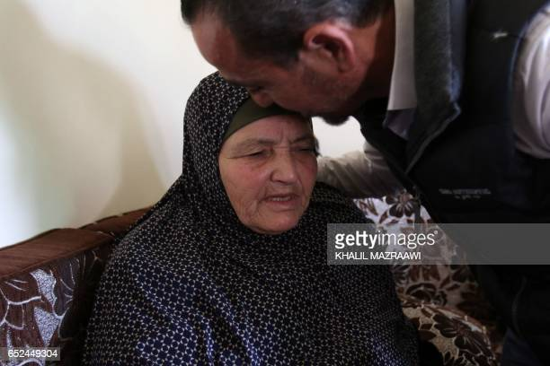A relative of Ahmad Dakamseh kisses the forehead of Ahmad's mother at her home in Irbid 90 kilometres north of the capital Amman on March 12 upon...