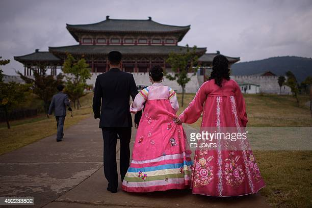 A relative of an engaged couple holds the traditional Korean 'hanbok' dress of the bride as they prepare to take their wedding photos at a 'Folk...