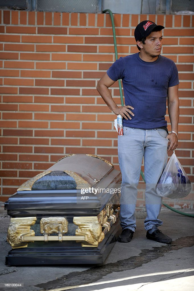 A relative of an inmate stands beside an empty coffin for a victim of a riot that broke out at the Uribana prison in Lara state, Venezuela, in January 26, 2013. At least 55 people were killed and 90 others wounded in clashes between prison gangs and security guards at a facility in northwest Venezuela, a hospital director said Saturday. AFP PHOTO/Leo RAMIREZ