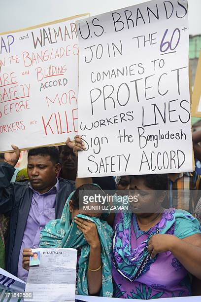 A relative of Bangladeshi worker who lost their life in a garment factory disaster is comforted by another as they gather with banners and placards...
