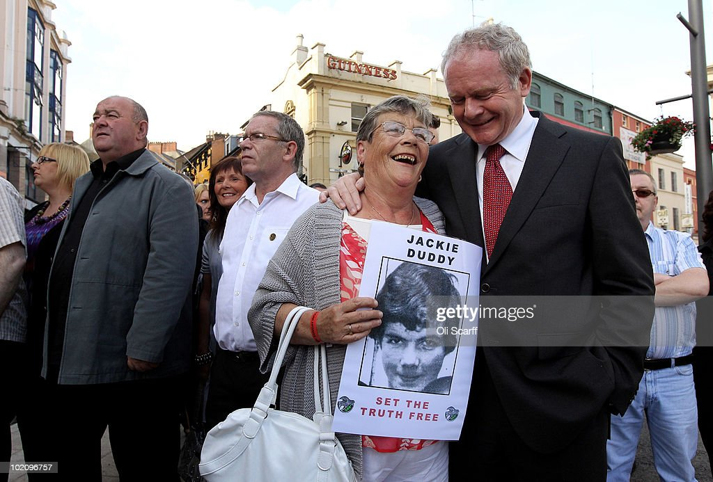 A relative of Bloody Sunday victim Jackie Duddy is comforted by <a gi-track='captionPersonalityLinkClicked' href=/galleries/search?phrase=Martin+McGuinness&family=editorial&specificpeople=211317 ng-click='$event.stopPropagation()'>Martin McGuinness</a> (R) as she marches from the Bogside area of Londonderry to the Guildhall to gain a preview of the Saville Report on June 15, 2010 in Londonderry, Northern Ireland. The long-awaited report from the Saville Inquiry, which was set up in 1998 and is estimated to have cost 191m GBP, will be announced by British Prime Minister David Cameron in the Commons today.