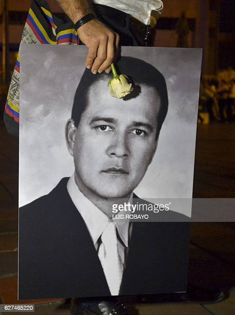 A relative of Carlos Barragan former deputy kidnapped and killed by the FARC in 2007 holds his portrait during a private ceremony where FARC leaders...