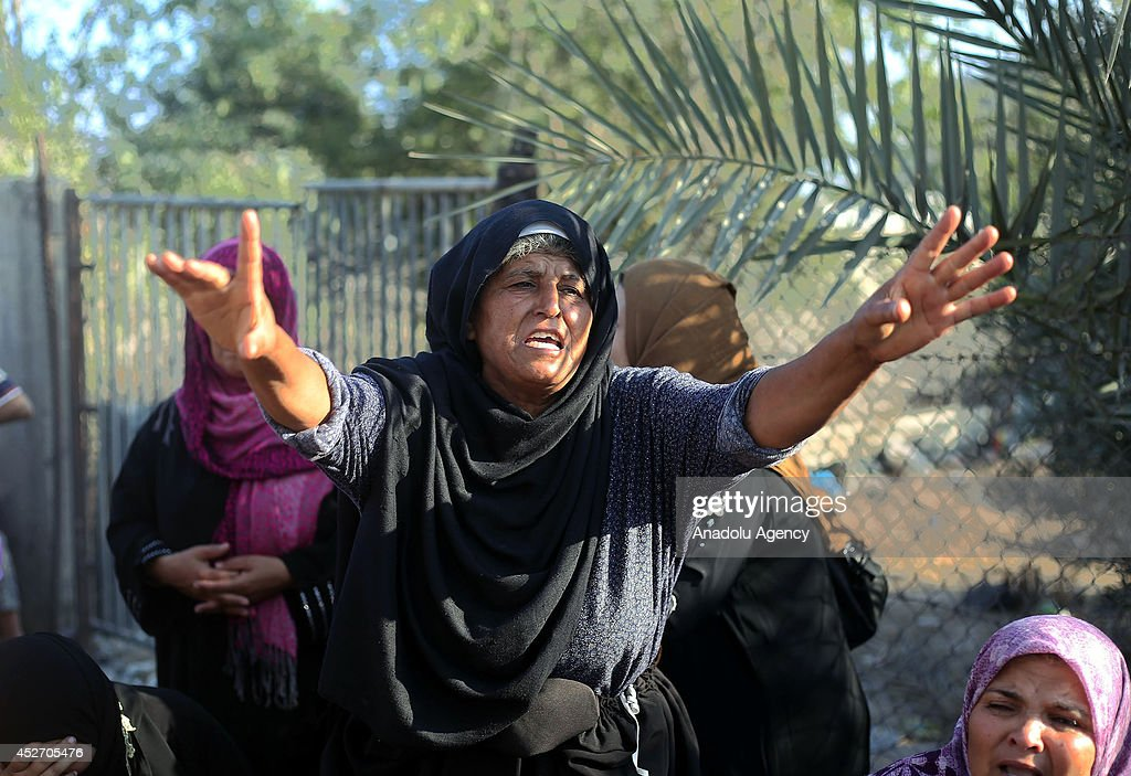 A relative of En-Neccar family mourns as search and rescue team and Palestinians search at the wreckage of a building, belongs to Palestinian En-Neccar family, in Khan Yunis, Gaza on July 26, 2014. Israeli assault, hit house of Palestinian En-Neccar family in Khan Yunis, killed 16 members of family and wounded 20 others in Gaza. The new fatalities raise Gaza's death toll from Israel's war to 900 since the beginning of this war on July 7.