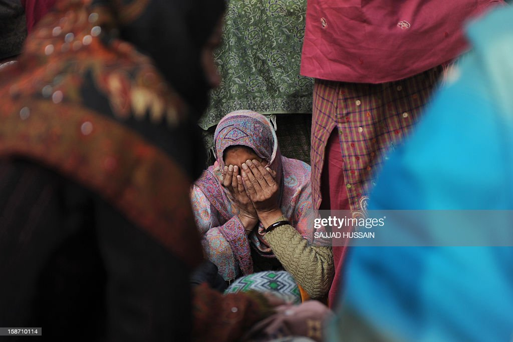 A relative of Indian policeman Subash Tomar mourns during his funeral in New Delhi on December 25, 2012. Tomar, a 47-year-old constable Indian policeman who was injured in clashes during a protest over a gang-rape in New Delhi has died. Tomar, a 47-year-old constable deployed at the India Gate monument on December 23 to control the protests, was beaten up by a mob and rushed to hospital by the police. AFP PHOTO/SAJJAD HUSSAIN