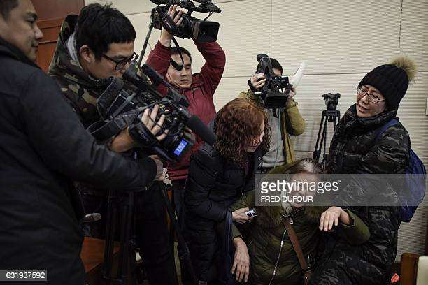 A relative of missing Chinese passengers aboard Malaysia Airlines Flight 370 that disappeared on March 8 2014 cries in front of journalists before a...