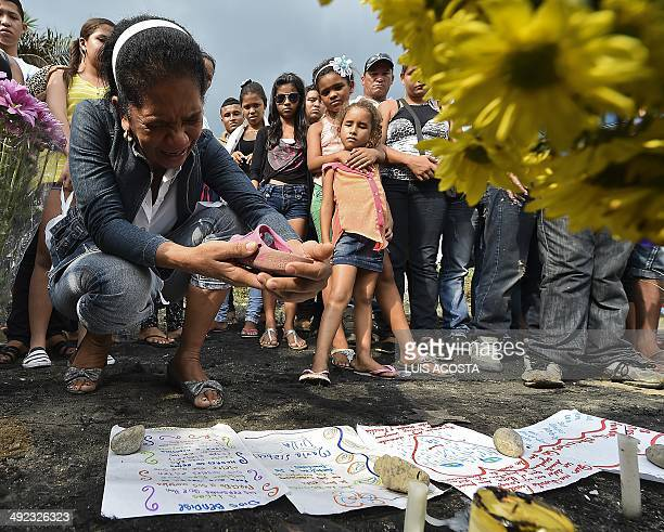 A relative of one of 32 chlidren burnt to death inside a school bus cries as she holds a shoe in Fundacion department of Magdalena Colombia on May 19...