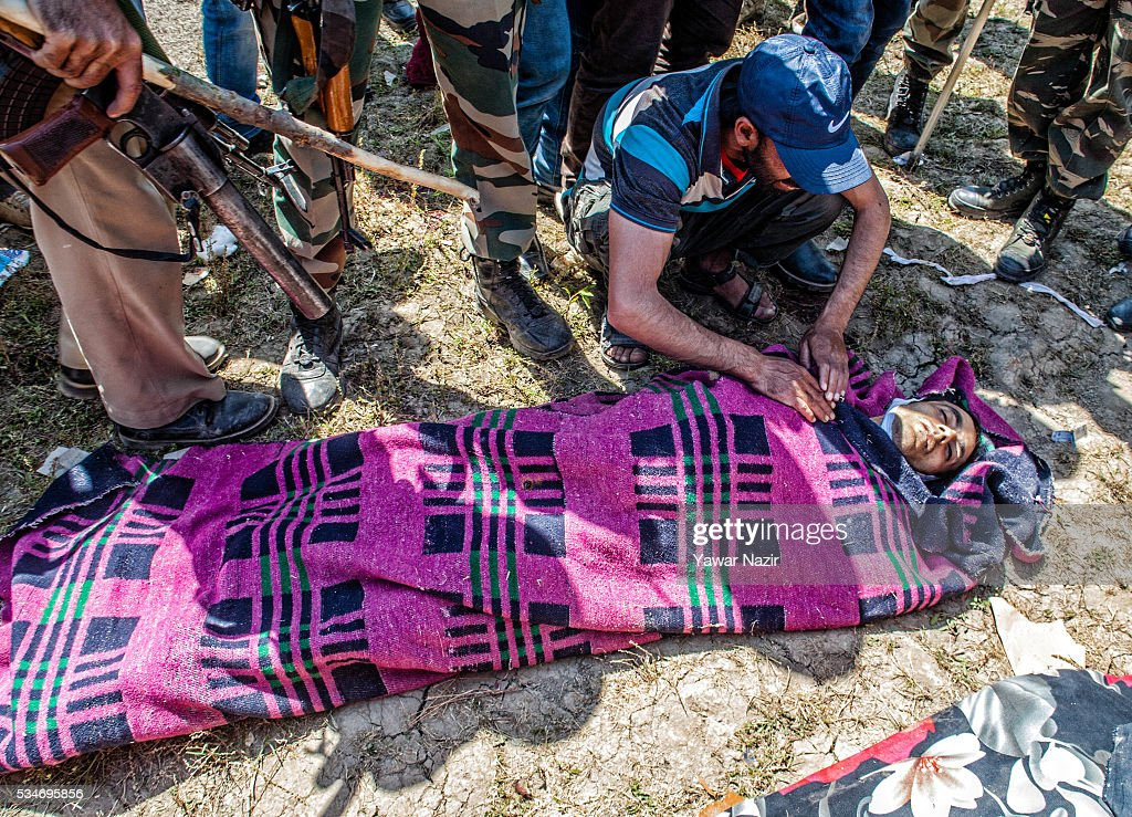 A relative of one of the local Kashmiri reble cries on seeing his body at the site after the gun battle between militants and Indian government forces on May 27, 2016 in Khonchpur, 40 kilometers (25 miles) west of Srinagar, the summer capital of Indian administered Kashmir, India. Six rebels and an Indian army soldier were killed in two separate gun battles in the north Kashmir just four days after the Indian police claimed to have gunned down two unidentified militants in Sarai Bala area of Srinagar, a claim contested by the locals who say they were just students putting up in the locality.