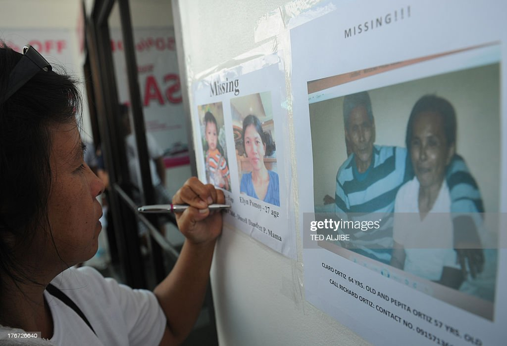 A relative of one of the missing passengers writes down contact numbers on pictures of missing kin displayed at the office of the ferry involved in a collision, in Cebu City, central Philippines on August 18, 2013. Philippine rescuers struggled in rough seas August 18, as they resumed a bleak search for 85 people missing in the country's latest ferry disaster, but insisted miracle survivor stories were possible.