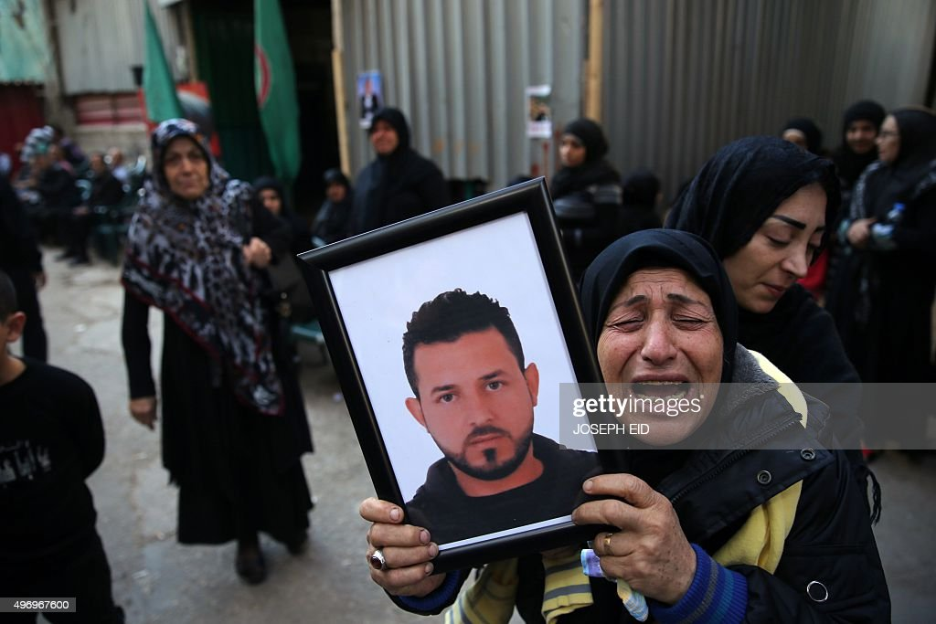 A relative of Samer Huhu who was killed in a twin bombing attack that rocked a busy shopping street in the area of Burj alBarajneh waves his portrait...