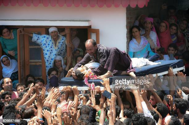 A relative of slain rebel Abid Ahmed wails over his body as women and other mourners look on during his funeral procession in the village of Hajinar...