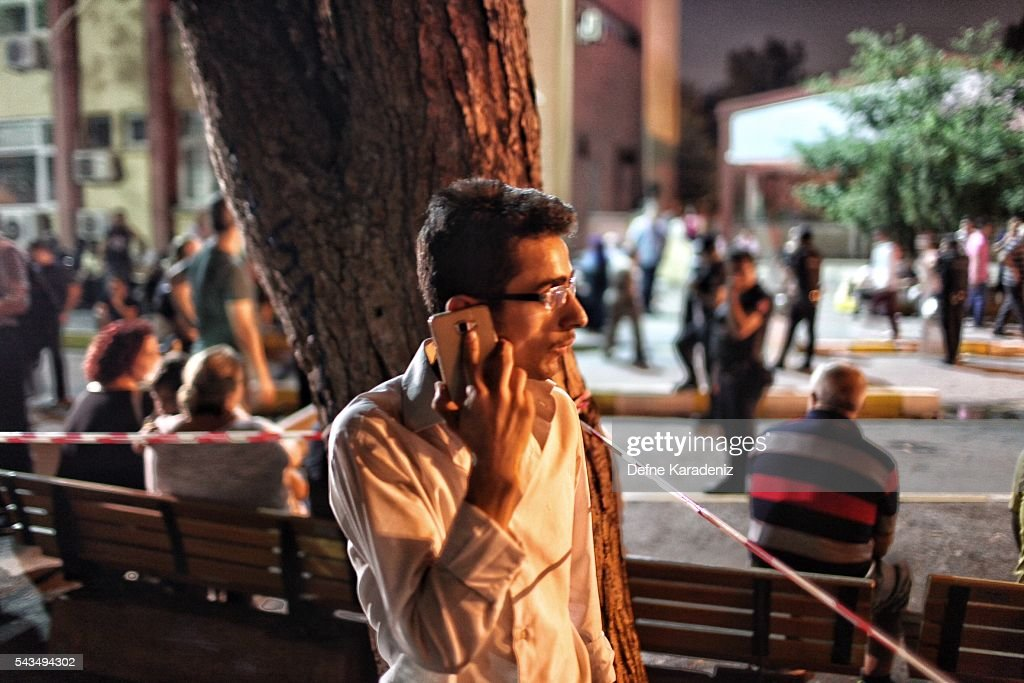 A relative of the Ataturk Airport suicide bomb attack victim wait outside Bakirkoy Sadi Konuk Hospital as he talks on phone, in the early hours of June 29, 2016 in Istanbul, Turkey. Three suicide bombers opened fire before blowing themselves up at the entrance to the main international airport in Istanbul, killing at least 31 people and wounding 147 people according to Justice Minister Bekir Bozdag.