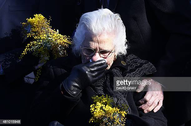 A relative of the Australian victims of Malaysia Airlines flight MH17 reacts before placing a floral tribute at a memorial unveiled on the first...