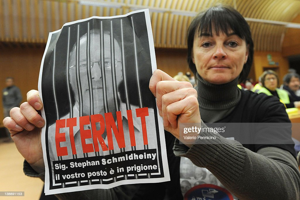 A relative of the victims holds signs saying 'Mr Stephan Schmidheiny, your place is in jail' during the Eternit verdict reading on February 13, 2012 in Turin, Italy. The Turin court has convicted Swiss billionaire Stephan Schmindheiny and Belgian baron Jean-Louis de Cartier for 16 years each after they were accused of involuntary manslaughter and disregard for workplace safety regulations, after a three year trial. Around 1500 relatives and friends of the alleged 3000 victims attended the final day of the trial with 160 foreign delegations attending from all over the world.