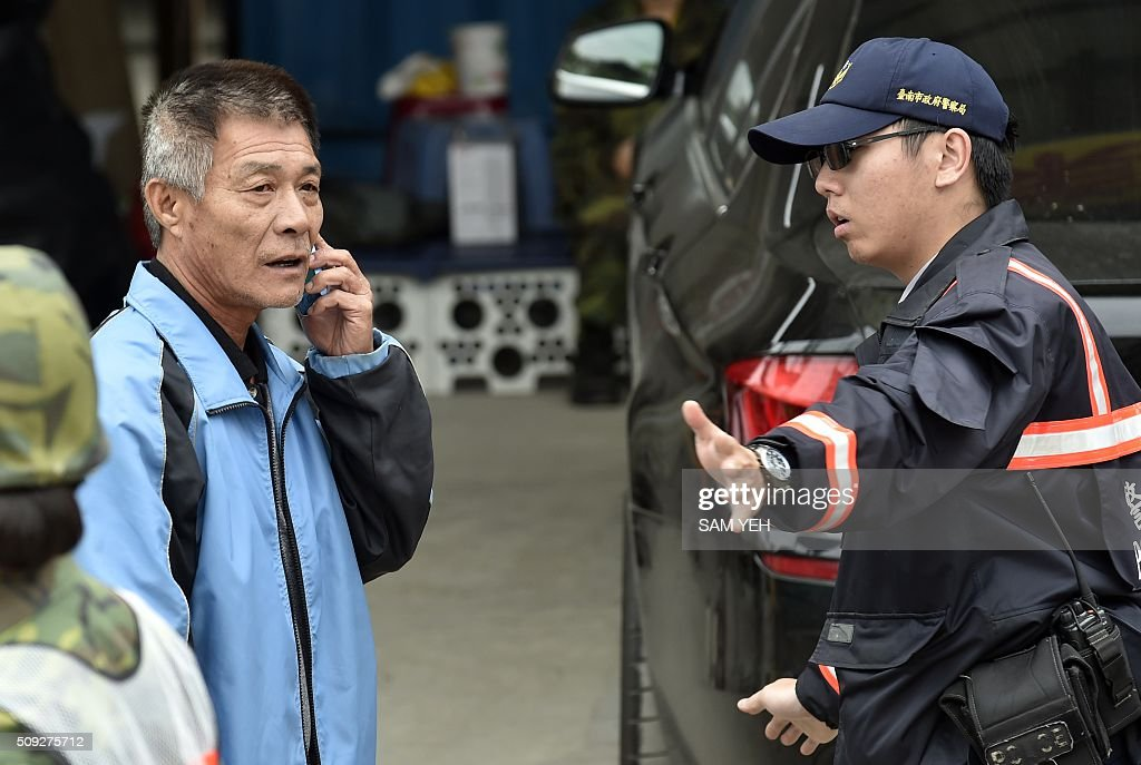 A relative of trapped family members inside the Wei-Kuan complex which collapsed in the 6.4 magnitude earthquake, talks on a phone in the southern Taiwanese city of Tainan on February 10, 2016. The developer of a Taiwan apartment complex that collapsed during a strong earthquake was arrested February 9, as rescuers reported hearing signs of life in the rubble where some 100 people are still trapped. AFP PHOTO / Sam Yeh / AFP / SAM YEH