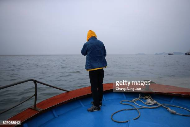 A relative of victim passenger of the sunken Sewol ferry watche workers lifting the boat in waters off Jindo on March 24 2017 in Jindogun South Korea...