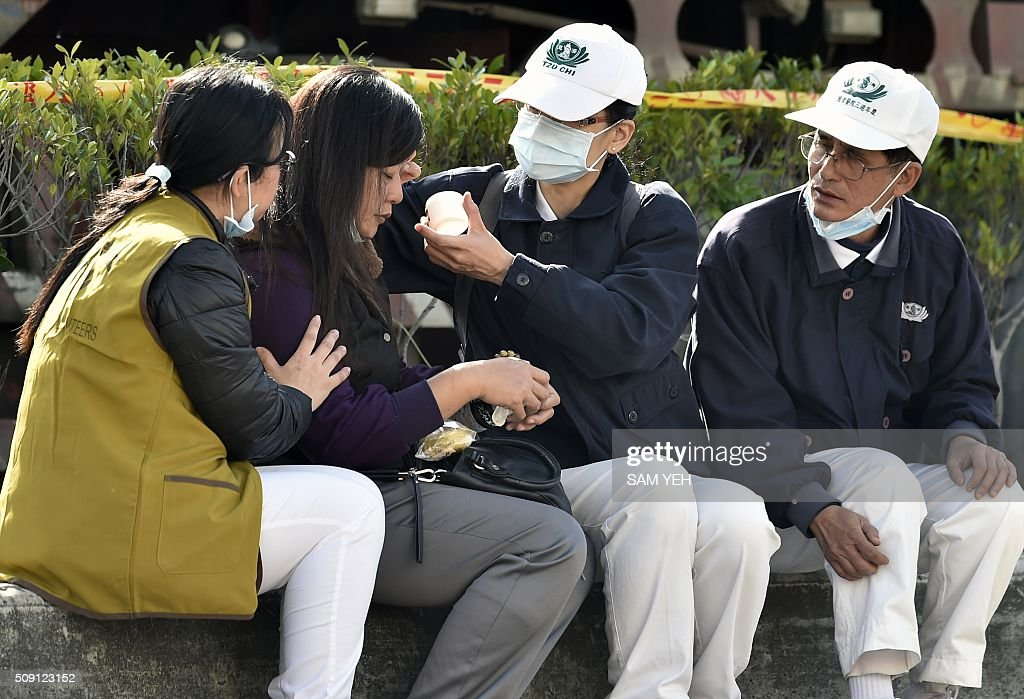 A relative (2ndL) of victims trapped inside the Wei-Kuan complex during the 6.4 earthquake is cared for by volunteers in Tainan, southern Taiwan, on February 9, 2016. Rescuers deployed heavy machinery in a renewed effort to locate more than 100 people trapped in the rubble of a Taiwan apartment complex felled by an earthquake as the 72-hour 'golden window' for finding survivors passed. AFP PHOTO / Sam Yeh / AFP / SAM YEH